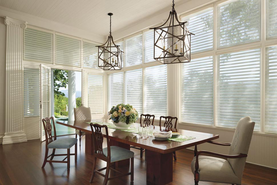 Large traditional dining room with multiple white custom window shades by Hunter Douglas