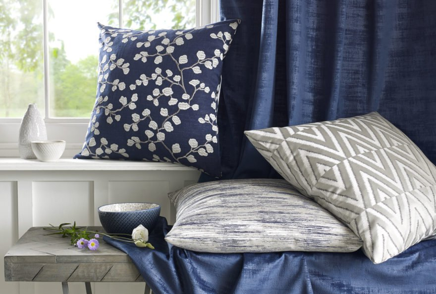 Navy blue fabric curtains with grey pillows on wood bench near a window