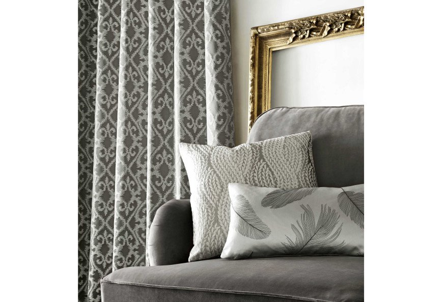 Grey pattern fabric curtains with on charcoal couch and grey pattern cushions in a living room