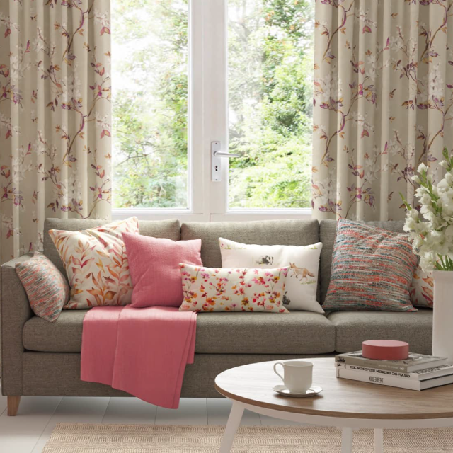 Floral pattern fabric curtains with matching cushions, a wood coffee table and a woven rug in a living room