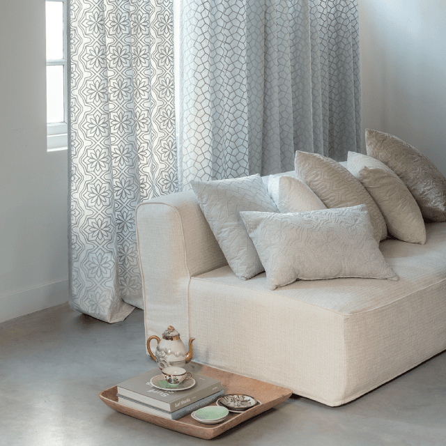 Pattern curtains with beige couch and tonal cushions with tea set on wood serving tray