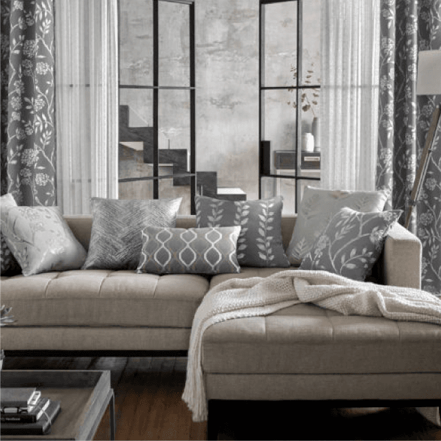 Greyscale living room with pattern fabric and sheer curtains with matching grey cushions
