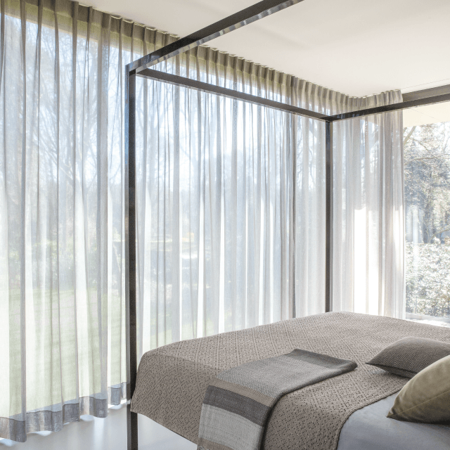 Sheer taupe fabric curtains in bedroom with metal bed frame and beige bedding