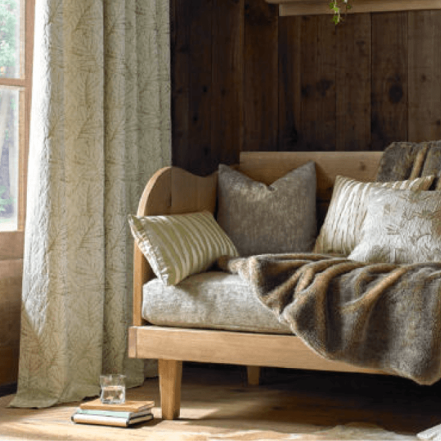 Pattern fabric curtains with rustic wood wall, floors, bench and a faux-fur throw