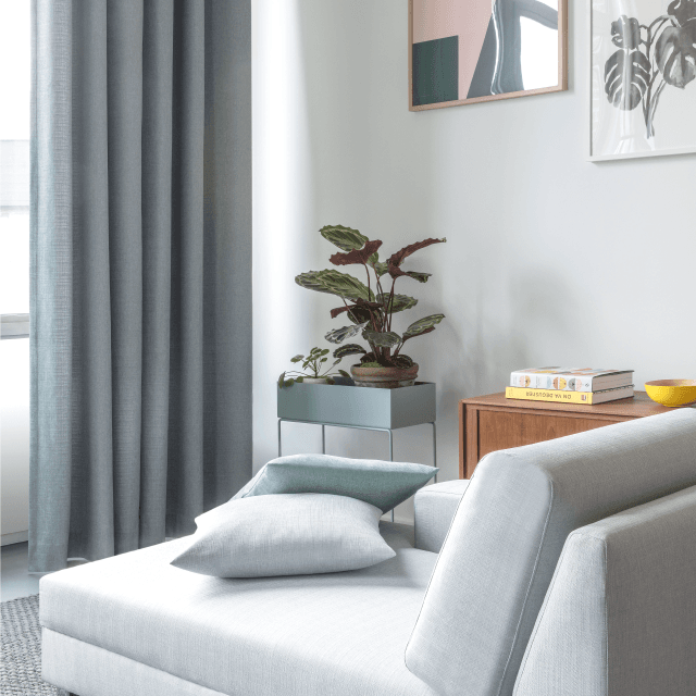 Grey fabric curtains in a contemporary room with light grey couch, cushions and framed artwork