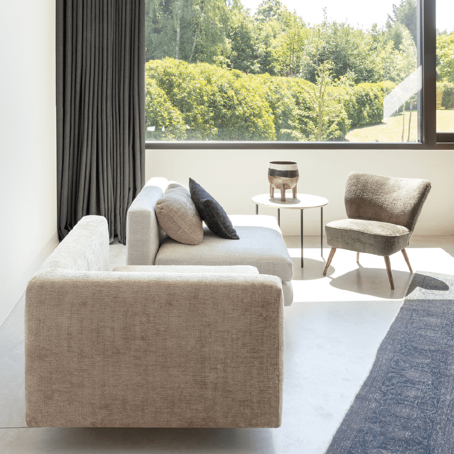 Dark blackout curtains in a sunny room with beige furniture and a blue area rug